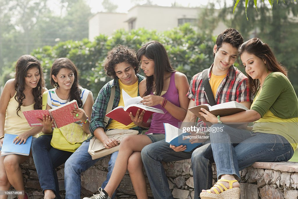 Group of young students sitting on stone wall and learning together : Stock Photo