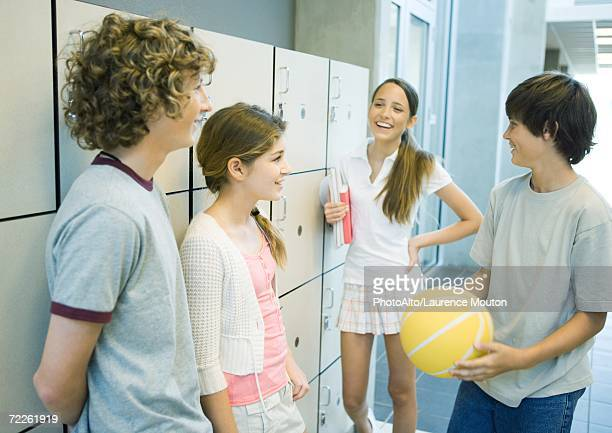 Group of young teens standing together near school lockers