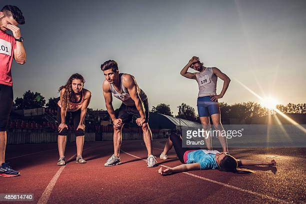 Group of young tired people taking breath after sports race.