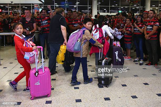 A group of young travellers arrive as Wanderers supporters wait in the arrivals hall for the Western Sydney Wanderers arrival at Sydney International...