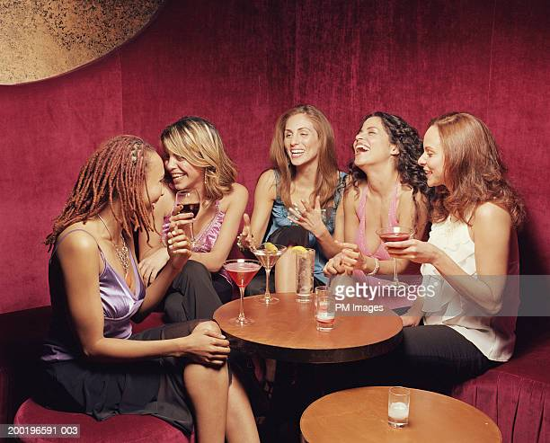 Group of young women at table in lounge, smiling