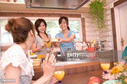 A group of young women cooking in the kitchen : Stock Photo