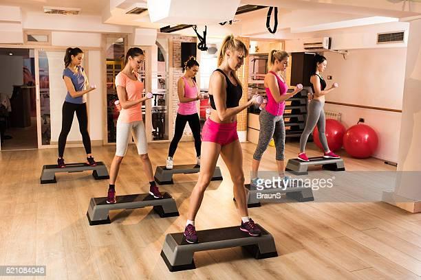 Gruppo di Giovane donna esercizio passo aerobica in palestra.