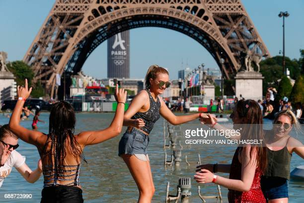 A group of young women laugh and play in the Fountain of Warsaw at the Gardens of the Trocadero with the Eiffel Tower on the back ground during warm...