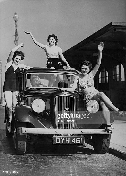A group of young women posing on their Austin Six saloon car on the seafront at Hastings East Sussex 19th April 1946