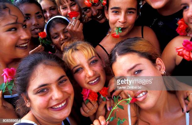A group of young women smiling with roses flowers on their lips during an artistic festival on May 2 2001 at Holguin Cuba The Festival of Young...