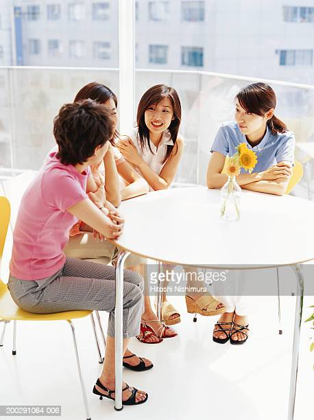 Group of young women talking at table, laughing