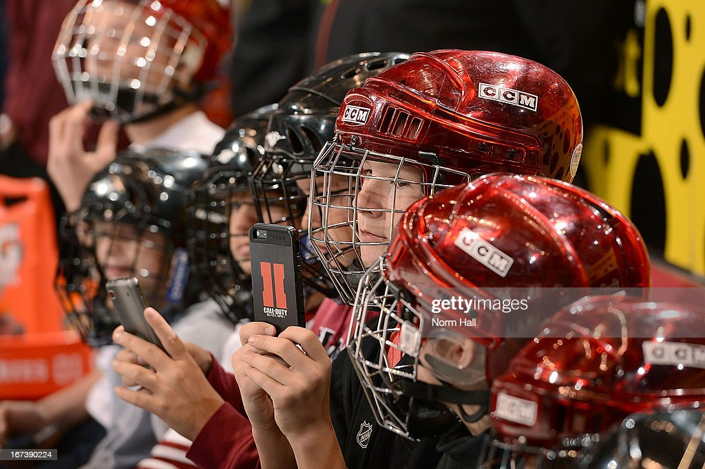 A group of youth hockey players use their cell phones to shoot photos during the pre-skate warm ups of the Phoenix Coyotes and San Jose Sharks game at Jobing.com Arena on April 24, 2013 in Glendale, Arizona.