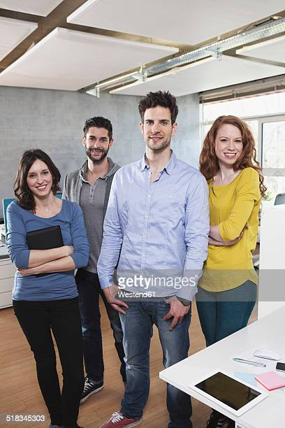 Group picture of four colleagues standing in the office
