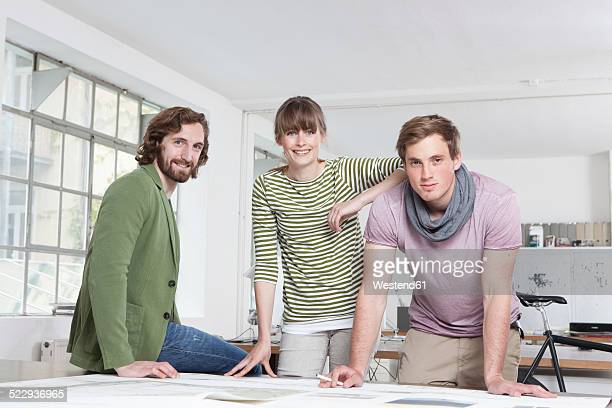 Group picture of three colleagues in a creative office