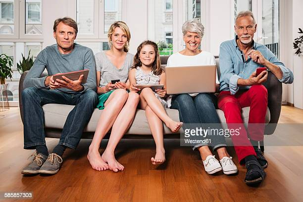 Group picture of three generations family with different digital devices sitting on one couch