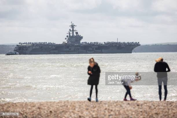 A group play on the beach as US Navy Nimitzclass aircraft carrier USS George HW Bush is anchored off the coast on July 27 2017 in Portsmouth England...