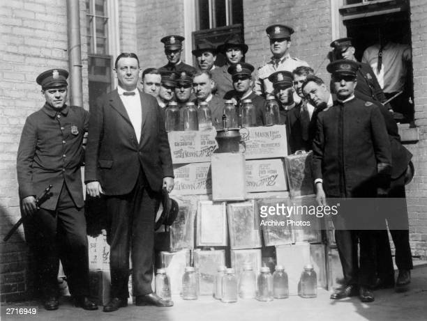 Group portrait of a police department liquor squad posing outdoors with cases of confiscated alcohol and distilling equipment during Prohibition