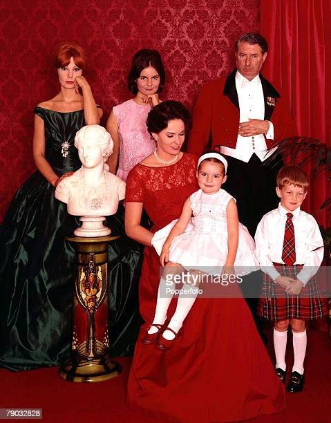 1962 A group portrait of an aristocratic family wearing fashionable and elegant eveningwear The two attractive young women that are standing are...