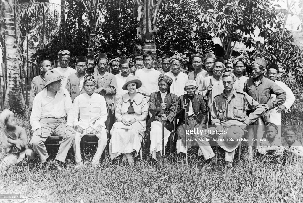 Group portrait of anthropologists Martin (1884 - 1937), (left) and Osa Johnson (1894 - 1953) with area officials, district officers and natives, before a trip upstream in Kinabatangan, British North Borneo (Sabah), now a state of Malaysia, 1920.
