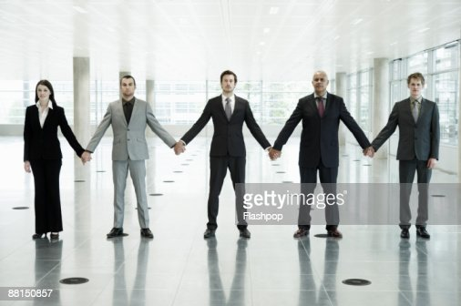 Group portrait of business people holding hands : Stock Photo