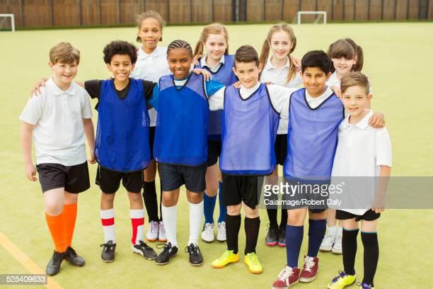 Group portrait of children wearing sport uniforms standing in school gym