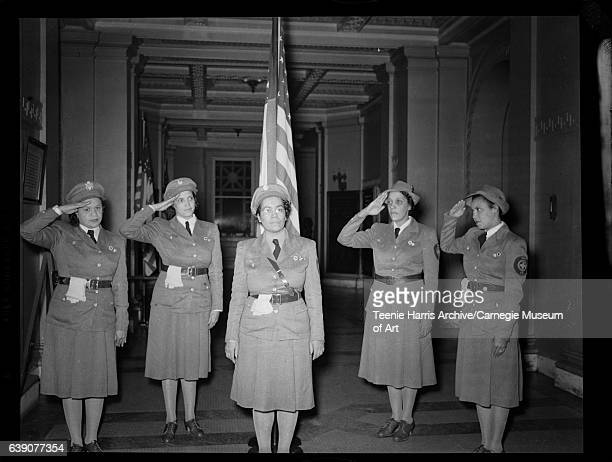 Group portrait of five women wearing military uniforms with USA patches with cross shape on shoulder including four saluting gathered in hallway of...