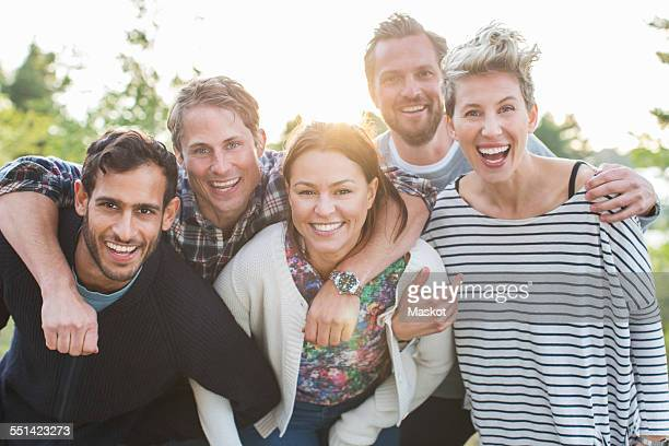 Group portrait of happy friends enjoying picnic at lakeshore