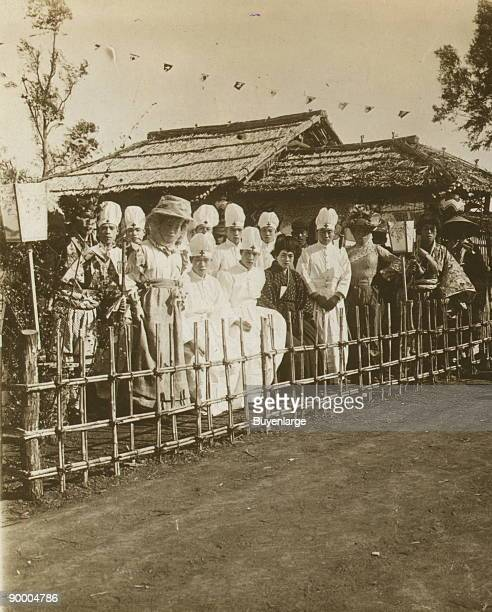 Group portrait of Japanese medical personnel and others dressed in Western and traditional style clothing seated near a building over which hang...