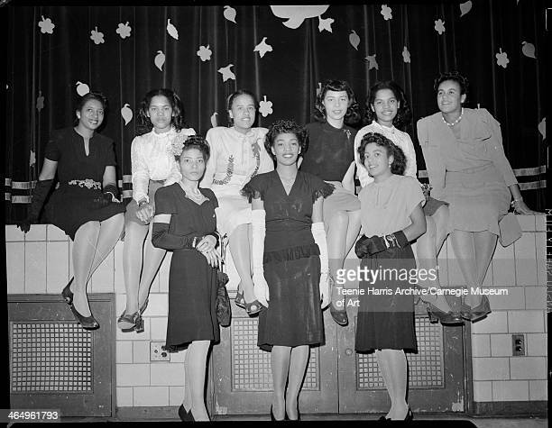 Group portrait of nine women members of Alpha Kappa Alpha Iota Chapter Sorority posed in front of stage with curtain decorated with leaves for Autumn...