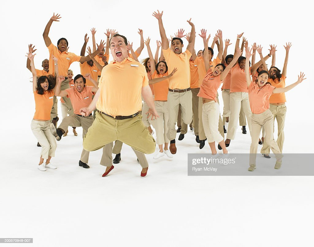 Group portrait of people wearing orange polo shirts, jumping : Stock Photo