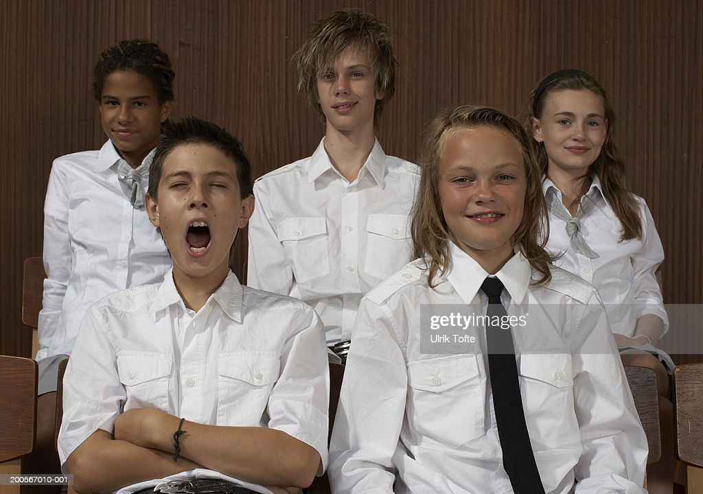 Group portrait of school children (12-14) in uniforms at assembly hall : Stock Photo