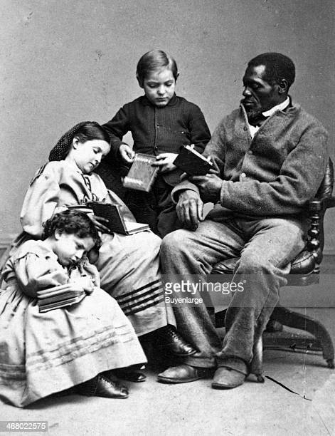 Group portrait of slave children identified only as Charley Rebecca and Rosa as they read books with an adult AfricanAmerican named Wilson New...