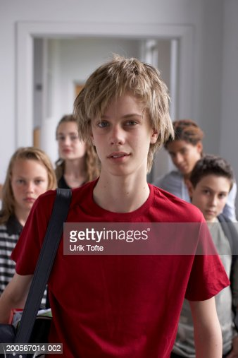 Group portrait of teenagers (12-14) at school corridor, focus on boy in foreground : Stock Photo
