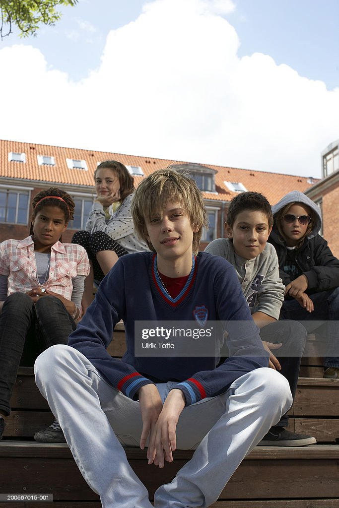 Group portrait of teenagers (12-14) sitting on steps in front of school : Stock Photo