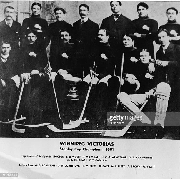 Group portrait of the Canadian hockey team the Winnipeg Victorias as they pose with the Stanley Cup 1901 Top row from left is Canadian M Hooper Burke...