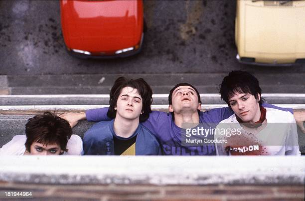 Group portrait of the Manic Street Preachers leaning out of the window of Martyn Goodacre's flat Old Kent Road London January 1991 LR Nicky Wire Sean...