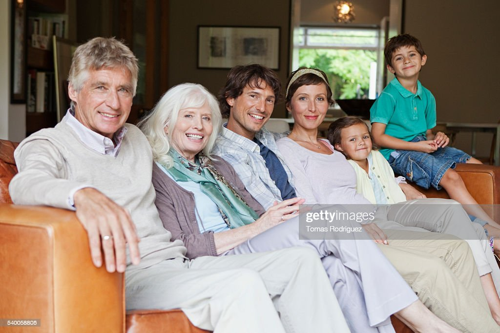 Group portrait of three generation family with two children (6-7, 8-9 years) on sofa