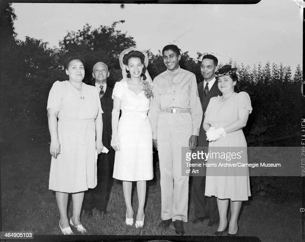Group portrait of three men including groom Charles L Page wearing military uniform and three women including bride Mary Jane Mitchell wearing white...