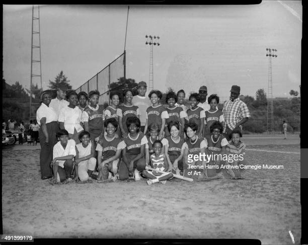Group portrait of women's Garfieldettes softball team with four men and some girls on Kennard Field Pittsburgh Pennsylvania circa 19551970