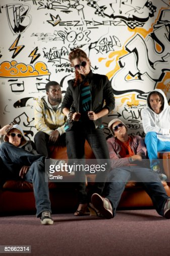 Group posing on couch in front of graffiti wall : Stockfoto