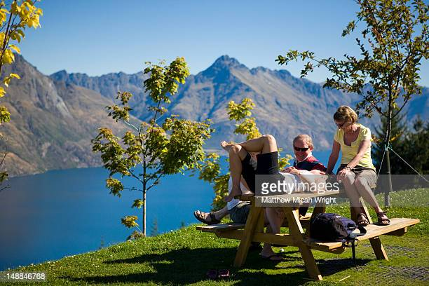 Group relaxing on picnic table by Lake Wakatipu with the Remarkables mountain range in background.