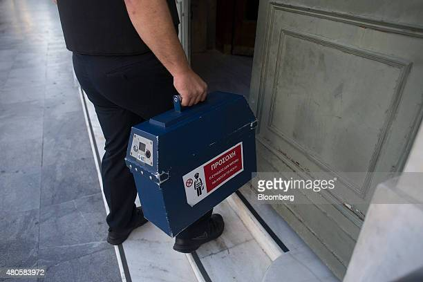 Group security guard delivers cash to a National Bank of Greece SA bank branch in Athens Greece on Monday July 13 2015 Greece has been in financial...