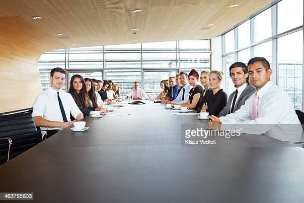 Group shot of 19 businesspeople at conferencetable