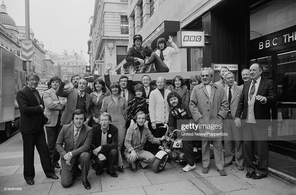 Group shot of BBC radio broadcasters posed together outside the entrance to BBC Paris Studio and Theatre in Lower Regent Street, London on 6th January 1981. Top row: Mike Reid and Judy Carne. Standing include: Roger Cook, Tom Vernon, Victor Spinetti, Joan Bakewell, Susie Barnes, Richard Baker, Dilys Watling, David Jacobs, Roy Plomley, Libby Purves, Sue MacGregor, John Walters and Brian Matthew. Front row includes: Terry Wogan, Lance Percival, Andrews Sachs, Dave Lee Travis, John Le Mesurier, Jack May and Michael Hordern.