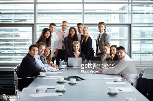 Group shot of businesspeople gathered around table : Stock Photo