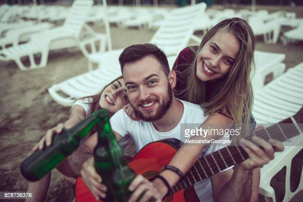 Groupe d'amitié souriant avec guitare acoustique, chant et boire de la bière
