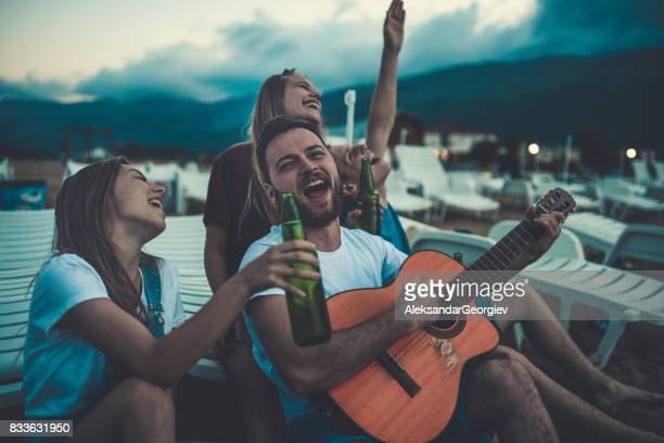 Group Smiling Friends with Acoustic Guitar Singing And Drinking Beer
