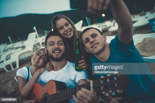 Group Smiling Friends with Acoustic Guitar Singing And Drinking Beer and Taking Selfie