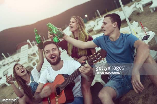 Groupe d'amis souriant avec le chant de la guitare acoustique sur la plage