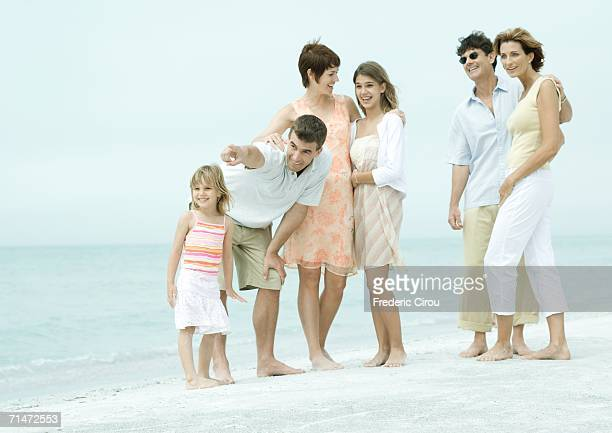 Group standing on beach, man pointing