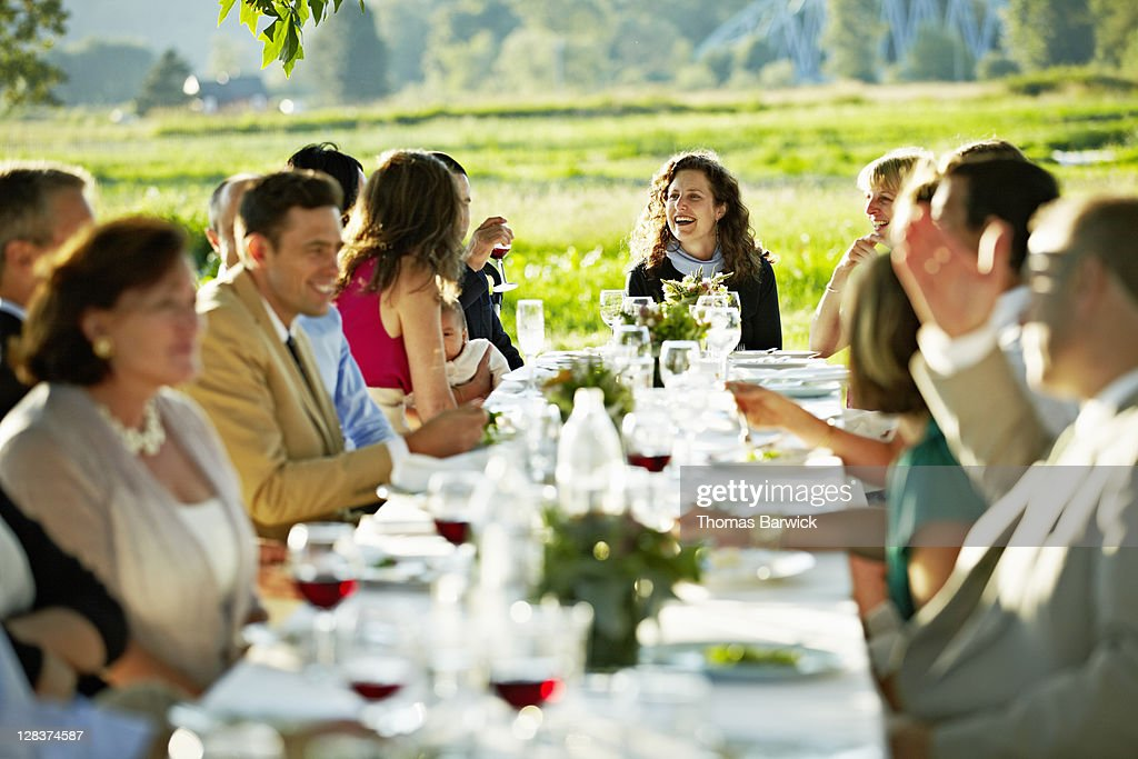 Group talking laughing and dining at table outside : Stock Photo