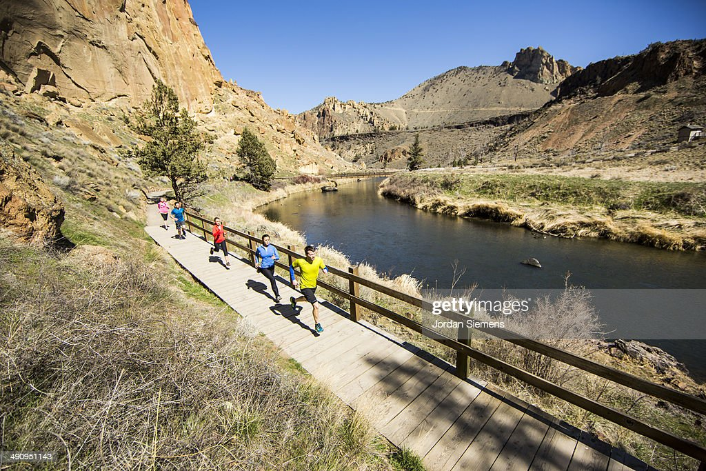 Group trail running near a river. : Stock Photo
