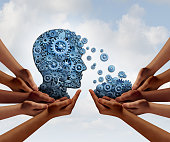 Group training and skill development business education concept with many diverse hands holding a bunch of gears transferring the wheels to a human head made of cogs as a symbol of acquiring the tools