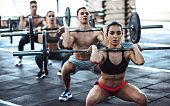 Group of sporty muscular people are working out in gym. gym training. Handsome shirtless men and attractive women are doing exercises with barbells. Weightlifting.